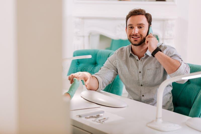 Homem considerável à moda que senta-se no salão de beleza que obtém o tratamento de mãos foto de stock