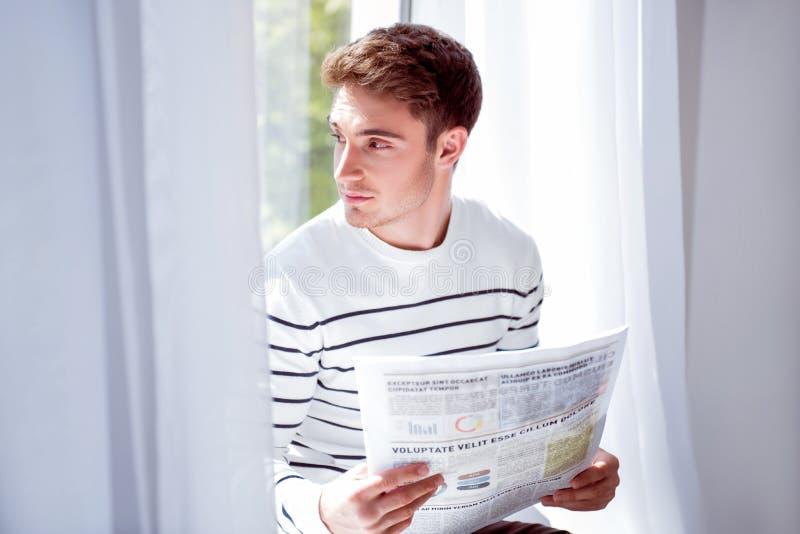 Homem considerável agradável que senta-se no peitoril da janela imagem de stock royalty free