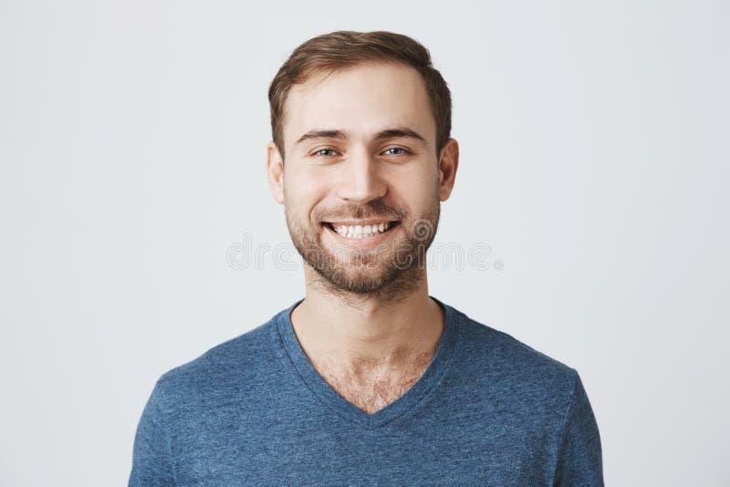 Homem considerável alegre com a barba que veste o t-shirt azul que sorri felizmente ao receber a notícia positiva Caucasian consi foto de stock royalty free