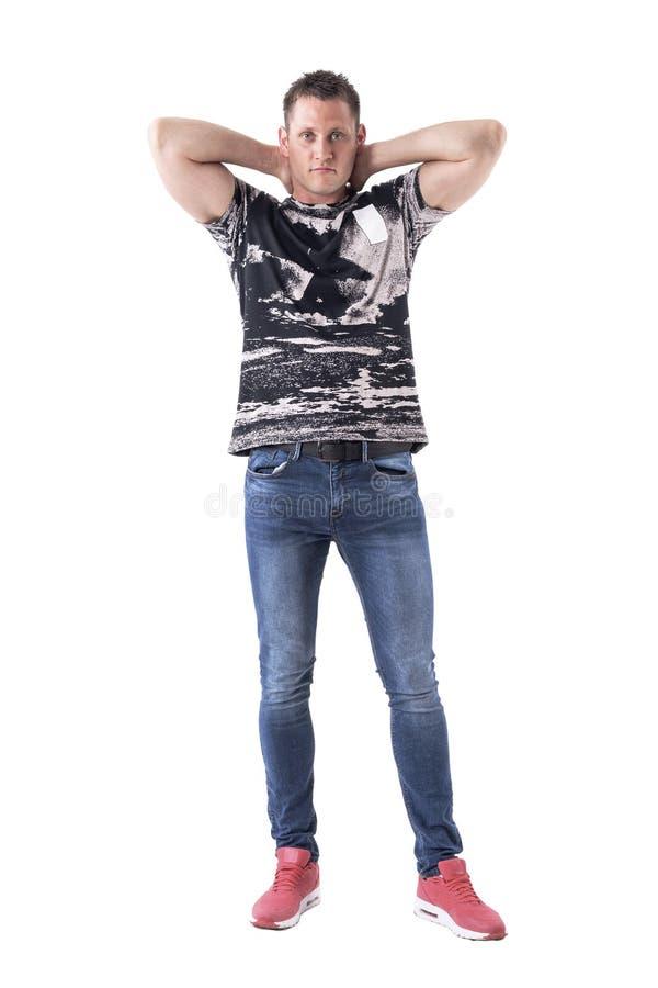 Homem considerável atlético que levanta com mãos atrás da cabeça com olhar intenso na câmera foto de stock