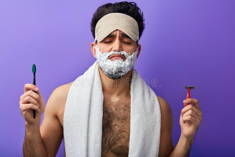 Homem considerável atrativo sonolento com os olhos fechados, barbeando a espuma em sua cara foto de stock royalty free