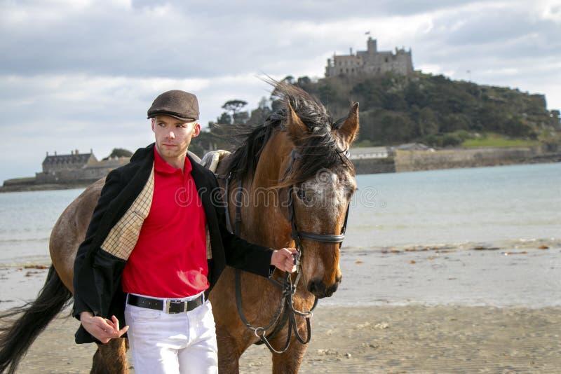 Homem considerável, cavaleiro do cavalo masculino que anda com seu cavalo na praia, tampão liso tradicional vestindo, calças bran fotos de stock