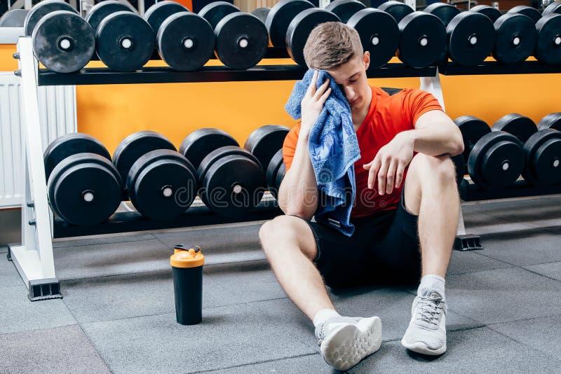 Homem considerável com a garrafa da água e da toalha que têm uma ruptura após o exercício no gym imagem de stock royalty free