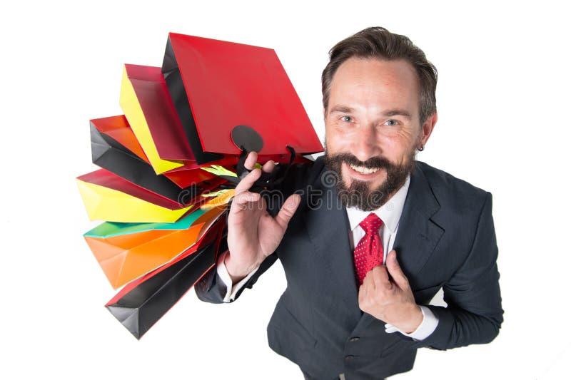 Homem considerável com lote da opinião superior dos sacos de compras homem no terno feliz do tempo e dos presentes da compra para imagens de stock