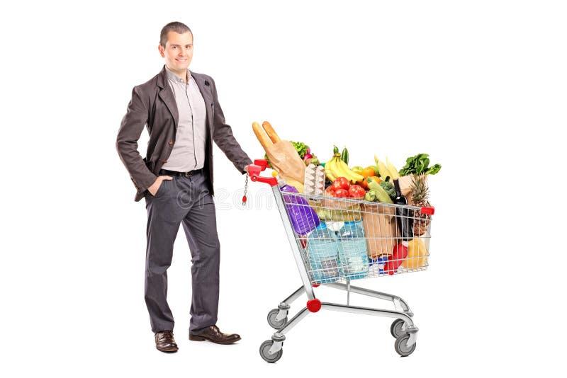 Homem considerável com o carrinho de compras completo dos mantimentos fotografia de stock royalty free