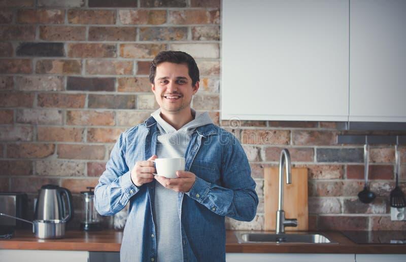 Homem considerável com o copo do chá ou do café que estão na cozinha imagens de stock