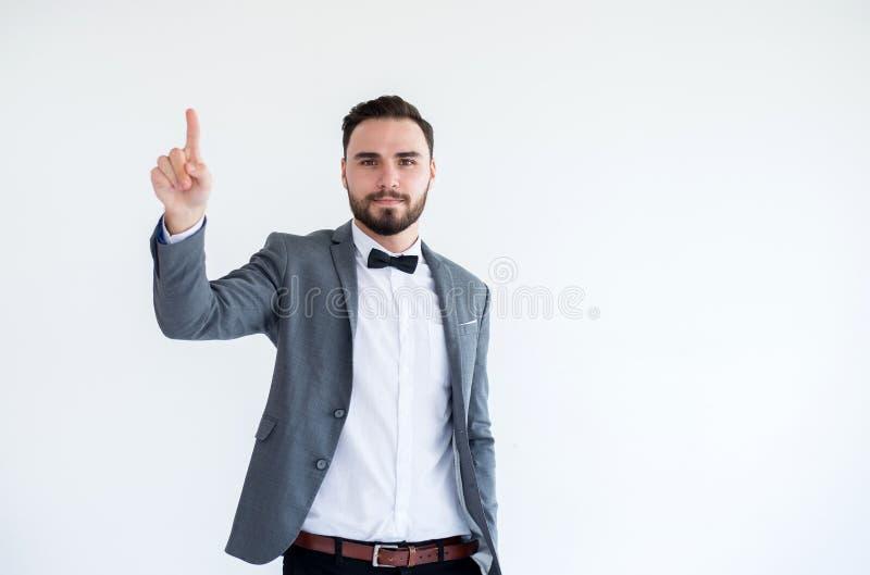 Homem considerável com o farpado no smoking e na mão formais da exibição do terno que aponta no fundo branco imagem de stock