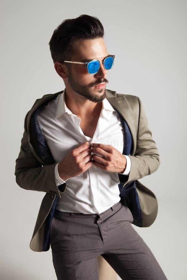 Homem considerável com os óculos de sol que abotoam sua camisa ao sentar-se fotos de stock