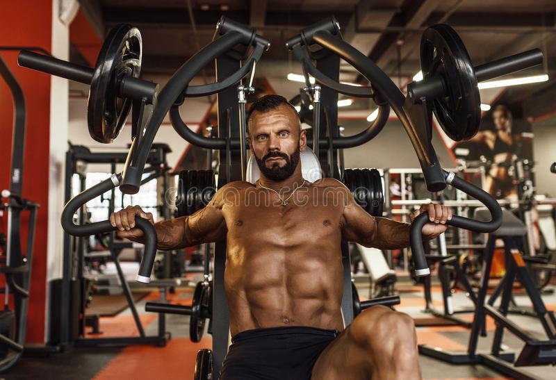 Homem considerável com os músculos grandes que dão certo no gym Halterofilista muscular que faz exercícios imagens de stock