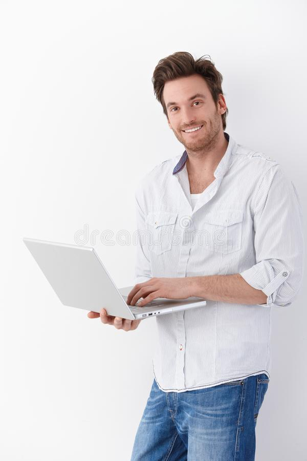 Homem considerável com sorriso do portátil
