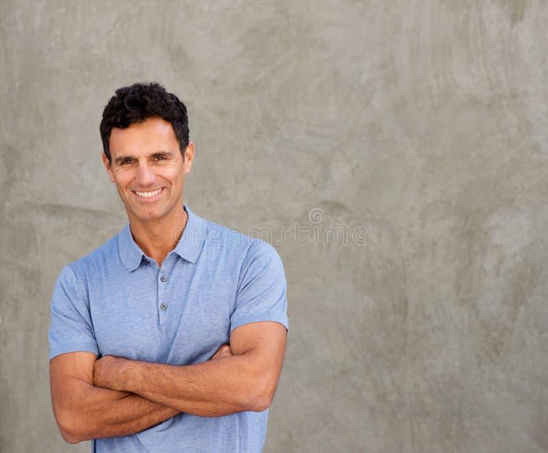 Homem considerável de sorriso que está pela parede com os braços cruzados fotos de stock
