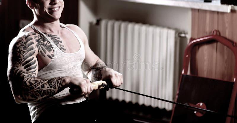 Homem considerável desportivo que faz exercícios no instrutor da casa imagem de stock