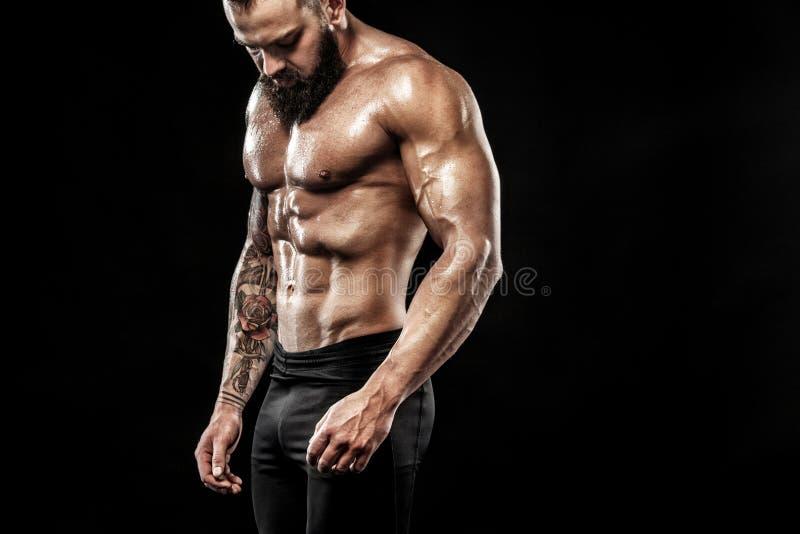 Homem considerável do ajuste que levanta vestir nas calças de brim com tatuagem Conceito do esporte e da forma isolado no fundo p fotografia de stock