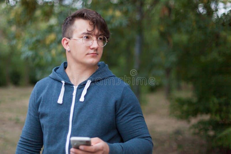 Homem considerável do caucasia com monóculos e telefone celular redondos fotografia de stock