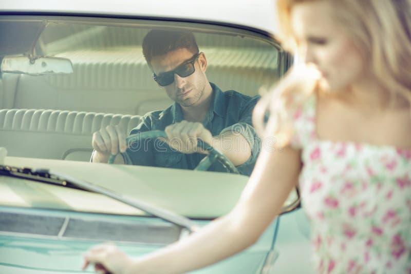 Homem considerável e à moda que dá a jovem mulher um elevador fotografia de stock