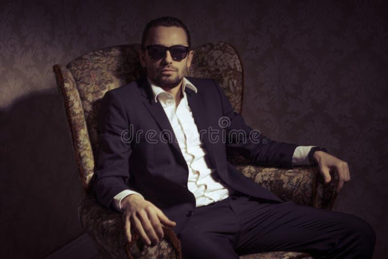 Homem considerável e elegante novo que sentam-se na cadeira que veste o terno preto e óculos de sol isolados sobre o fundo do vin fotos de stock