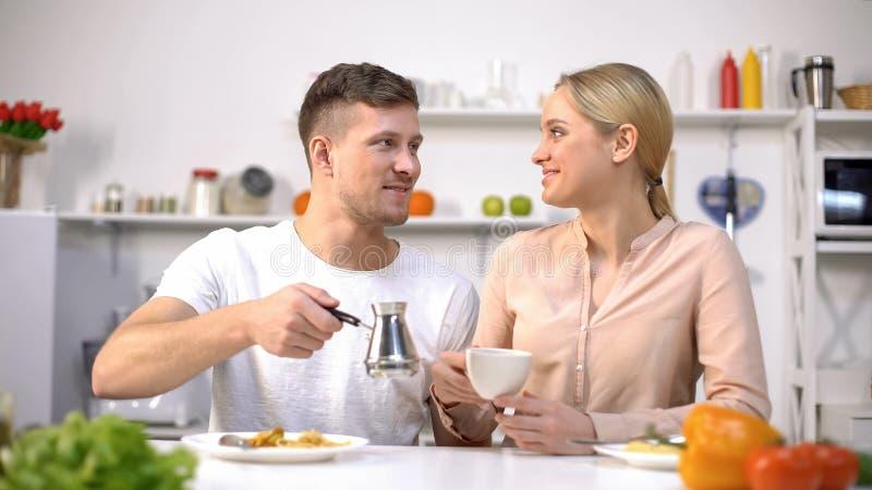Homem considerável e jovem mulher que fabricam cerveja o café, impulso da energia na manhã imagens de stock royalty free