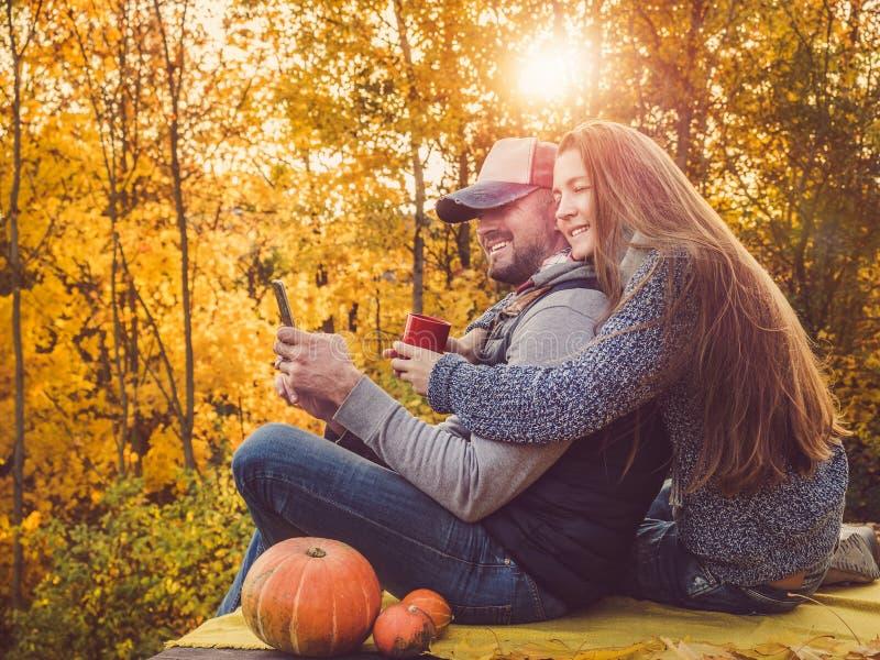 Homem considerável e mulher à moda que guardam um telefone fotos de stock