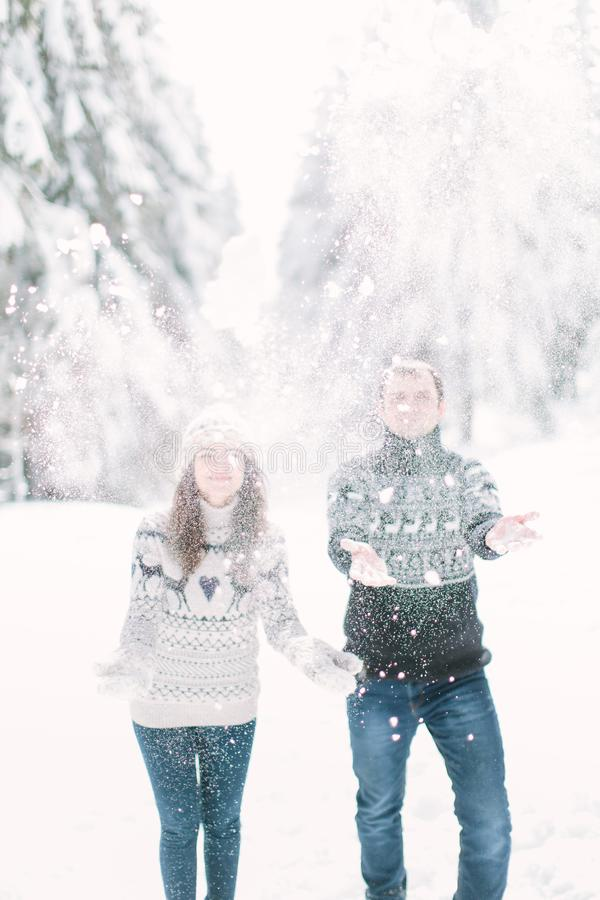 Homem considerável e sua pose bonita da mulher na neve e jogo com neve em uma floresta mágica do inverno fotos de stock
