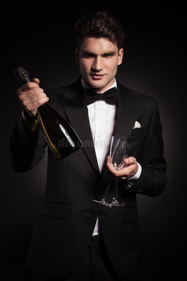 Homem considerável elegante que guarda uma garrafa do vinho fotografia de stock