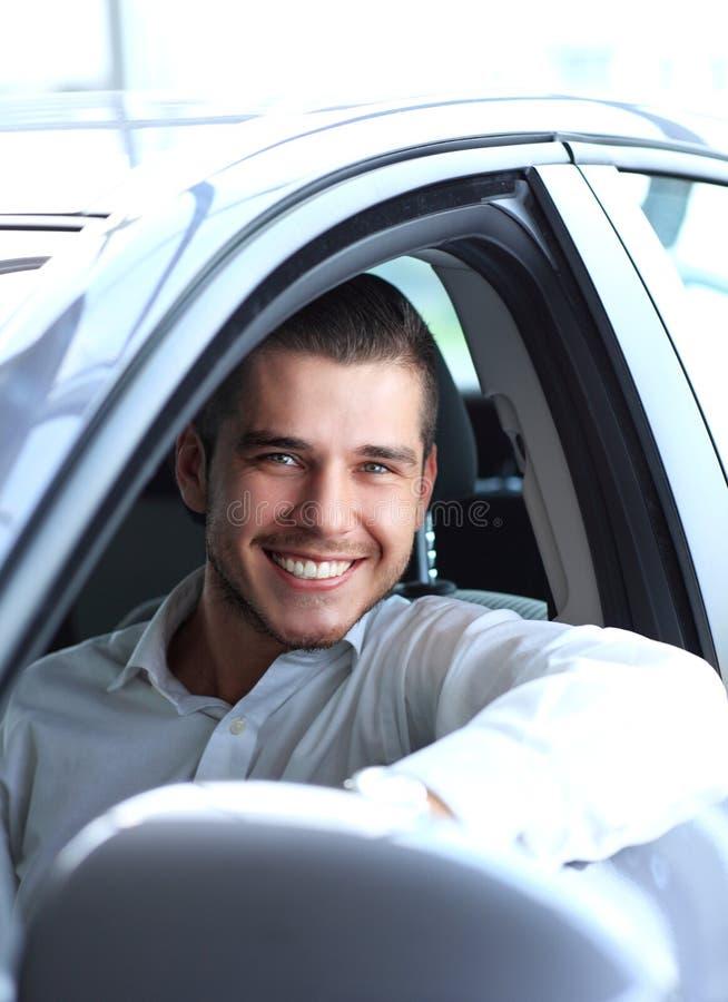 Homem considerável em no seu carro e sorriso novos imagem de stock royalty free