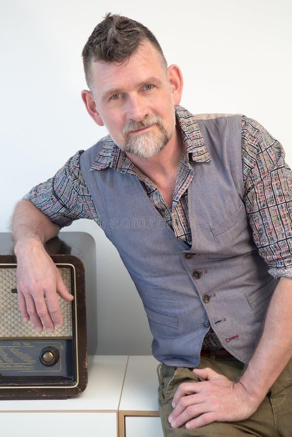 Homem considerável em seu 50s ao lado do rádio do vintage imagens de stock royalty free