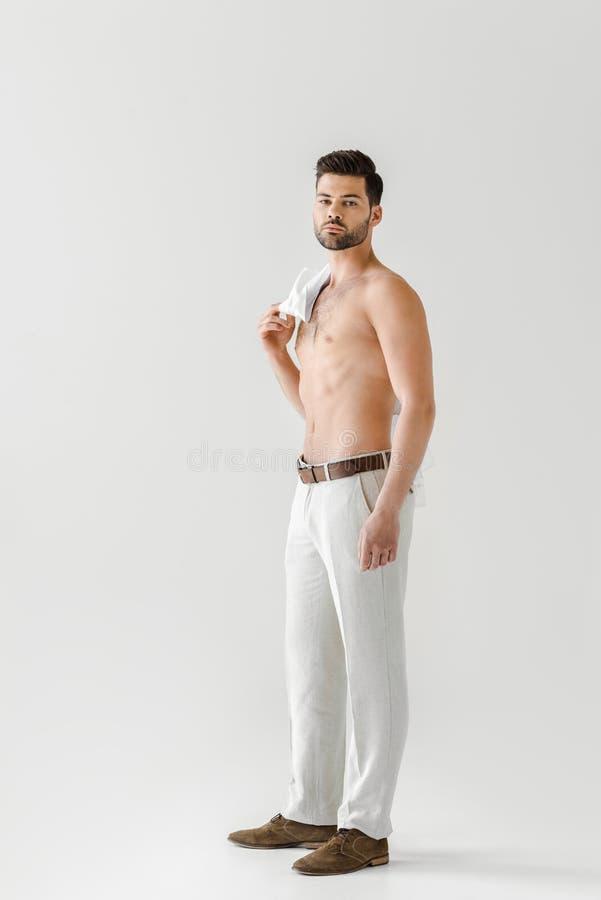 homem considerável em topless que levanta com a camisa no ombro fotografia de stock