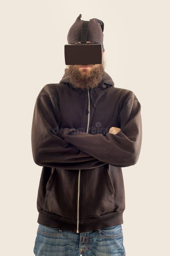 Homem considerável farpado novo que usa o dispositivo da realidade virtual fotografia de stock royalty free