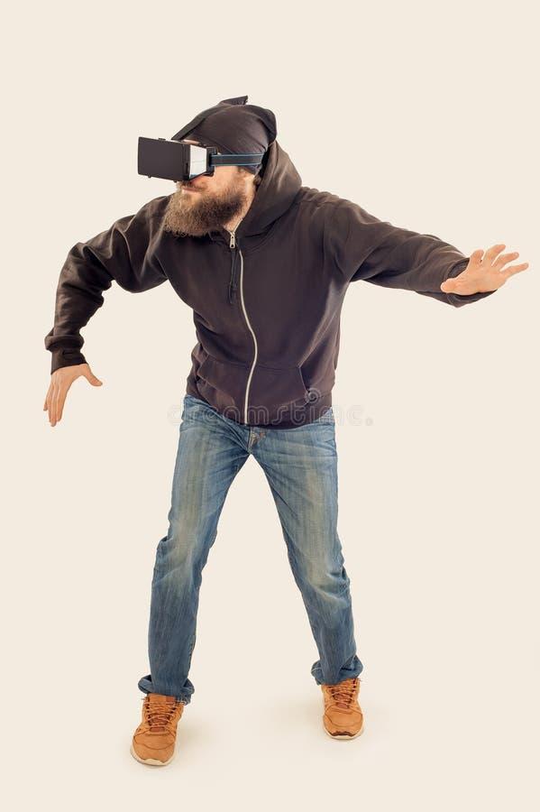 Homem considerável farpado novo que usa o dispositivo da realidade virtual imagens de stock royalty free