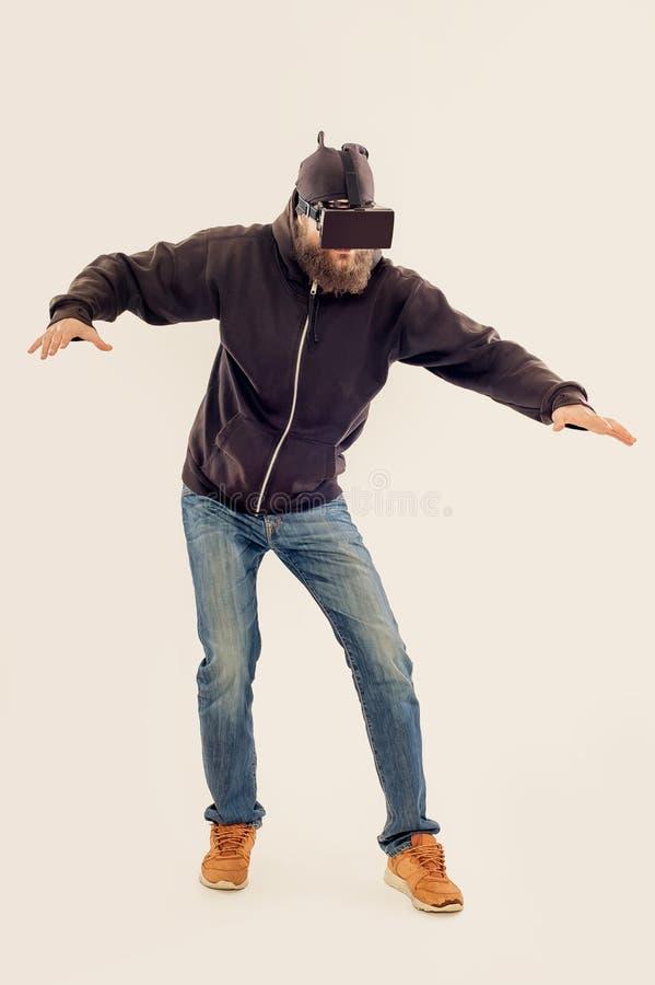 Homem considerável farpado novo que usa o dispositivo da realidade virtual fotos de stock