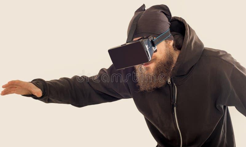 Homem considerável farpado novo que usa o dispositivo da realidade virtual foto de stock