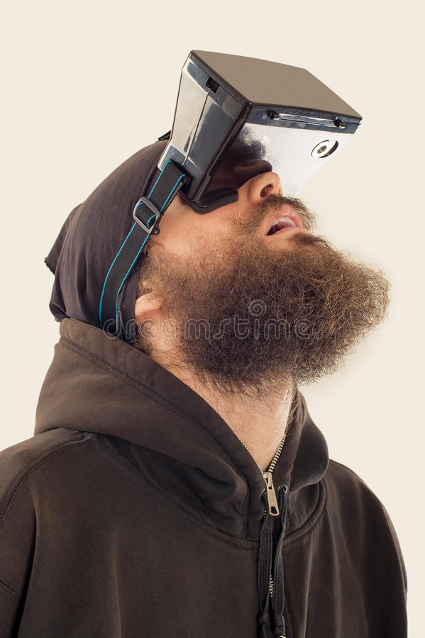 Homem considerável farpado novo que usa o dispositivo da realidade virtual fotografia de stock
