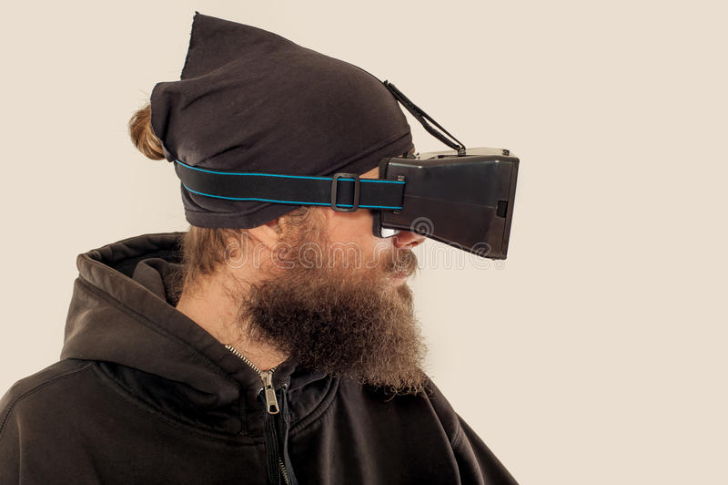 Homem considerável farpado novo que usa o dispositivo da realidade virtual foto de stock royalty free