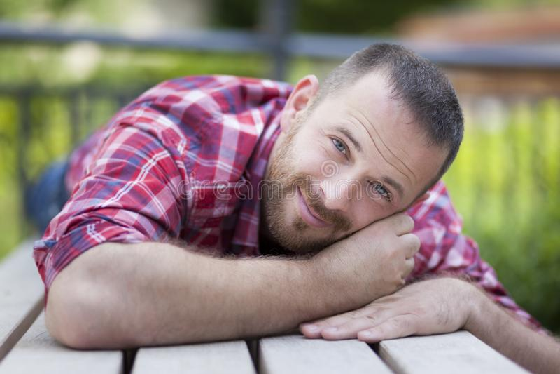Homem considerável farpado que encontra-se em um banco imagens de stock