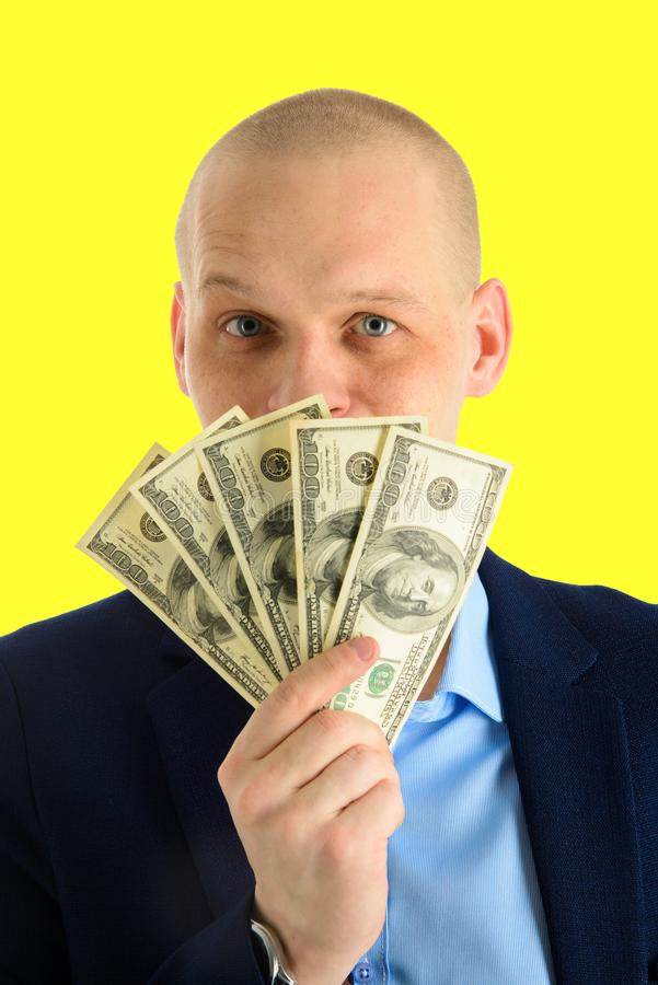 Homem considerável feliz em um terno que guarda o fã de cédulas do dólar, o homem de negócios e o dinheiro Isolado no fundo amare fotos de stock