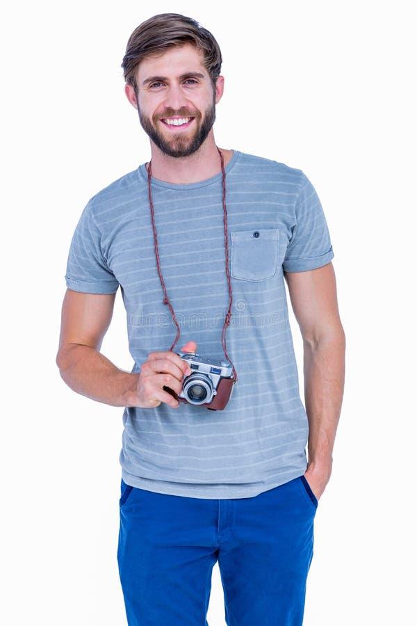Homem considerável feliz que olha a câmera e que guarda a câmera da foto fotografia de stock