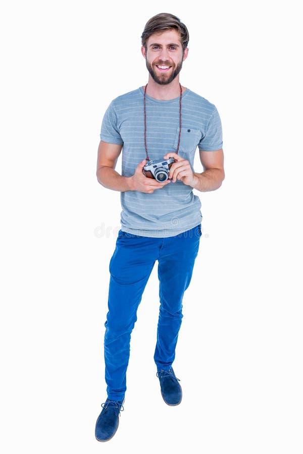 Homem considerável feliz que olha a câmera e que guarda a câmera da foto fotografia de stock royalty free