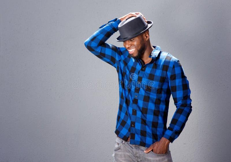 Homem considerável feliz que ri com mão ao chapéu fotos de stock