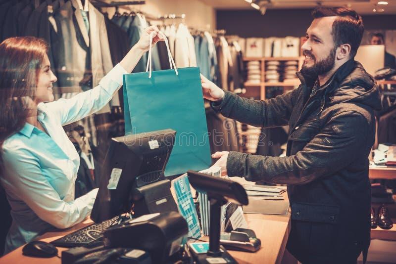 Homem considerável feliz que toma o saco de compras da vendedora em uma loja do terno fotos de stock