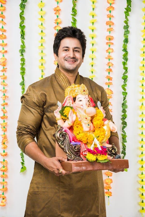 Homem considerável indiano no desgaste étnico que guarda um ídolo de Ganesh, dando boas-vindas ao deus em Ganesh Chaturthi/festiv imagens de stock royalty free