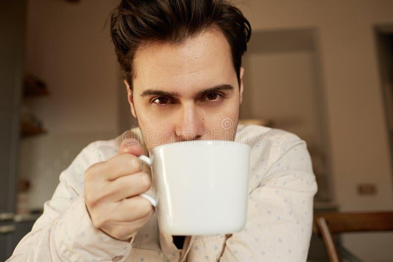 Homem considerável latino-americano que guarda a xícara de café branca em casa fotografia de stock royalty free