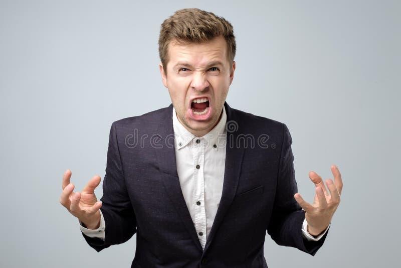 Homem considerável louco da raiva na gritaria estando ou em gritar do terno foto de stock royalty free