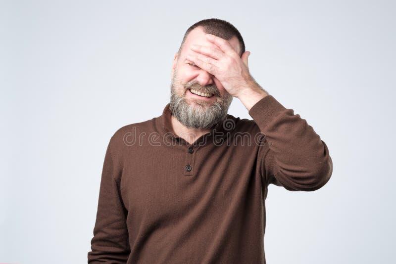 Homem considerável maduro que veste a roupa marrom que sorri e que ri com mão na cara que cobre os olhos foto de stock