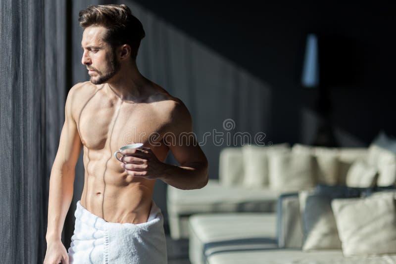 Homem considerável, muscular, novo que bebe seu café da manhã em um h foto de stock