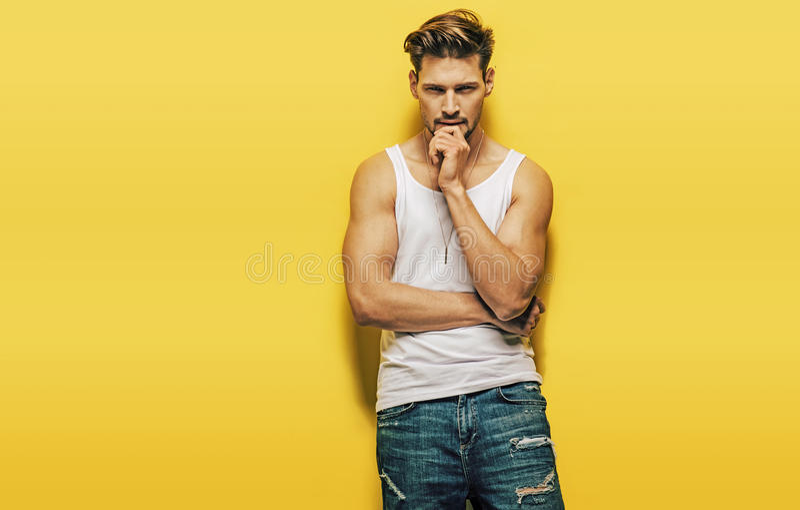 Homem considerável, muscular que levanta em um fundo amarelo foto de stock