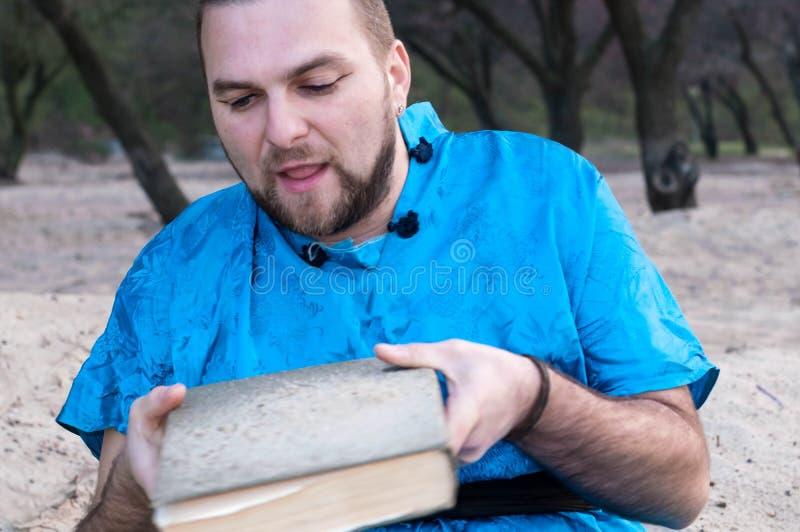 Homem considerável na areia deixando cair do quimono azul do livro imagem de stock