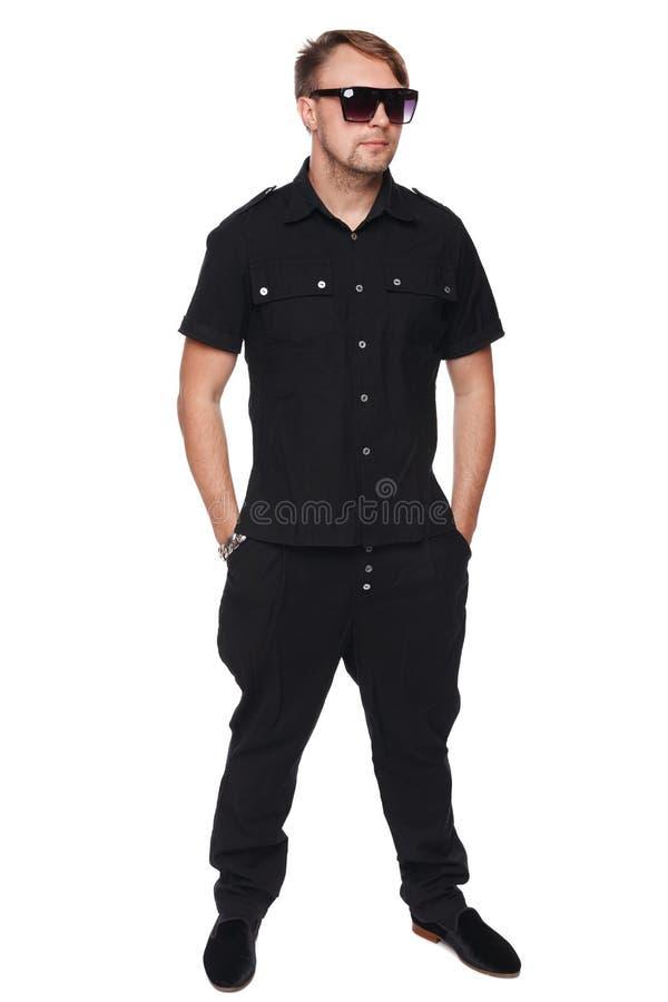 Homem considerável na camisa e nos óculos de sol que levantam do comprimento completo com mãos em uns bolsos, homem da forma Isol foto de stock royalty free