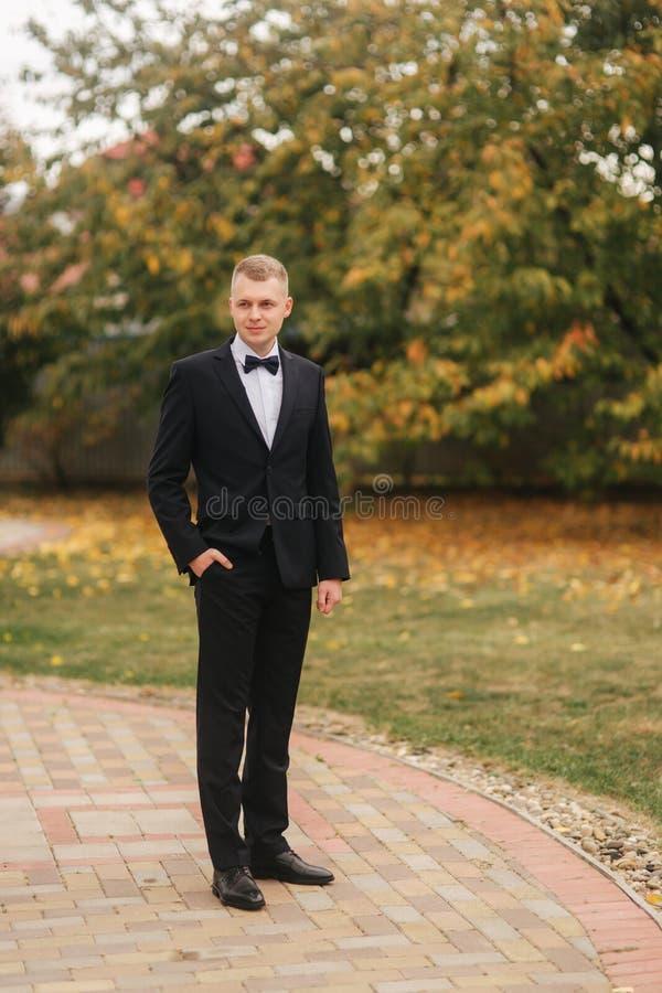 Homem considerável na posição preta do terno exterior no outono Noiva de espera do noivo fotografia de stock
