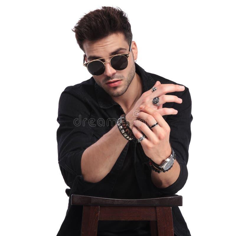Homem considerável na tabela de madeira que mostra seus braceletes e anéis imagens de stock