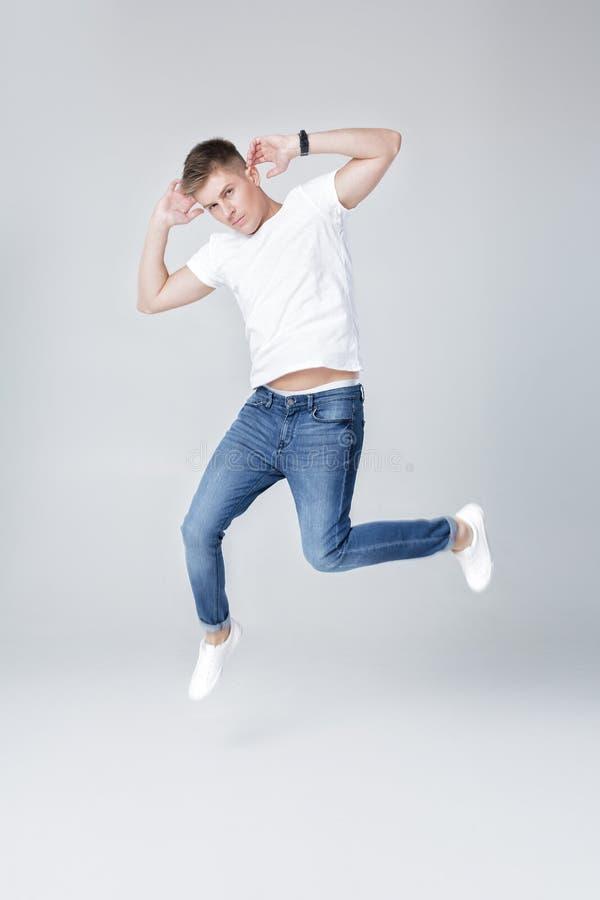 homem considerável nas calças de brim e no salto do revestimento imagem de stock royalty free